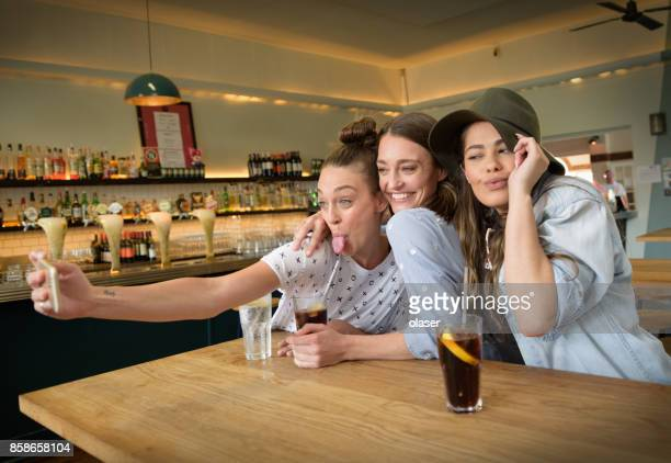 Young adults in bar taking selfie