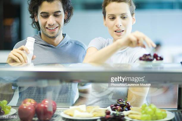 Young adults in exercise clothing, choosing snack in health club cafeteria