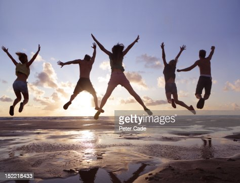 Young adults jumping in air on beach at sunset : Stock Photo