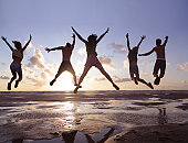 Young adults jumping in air on beach at sunset
