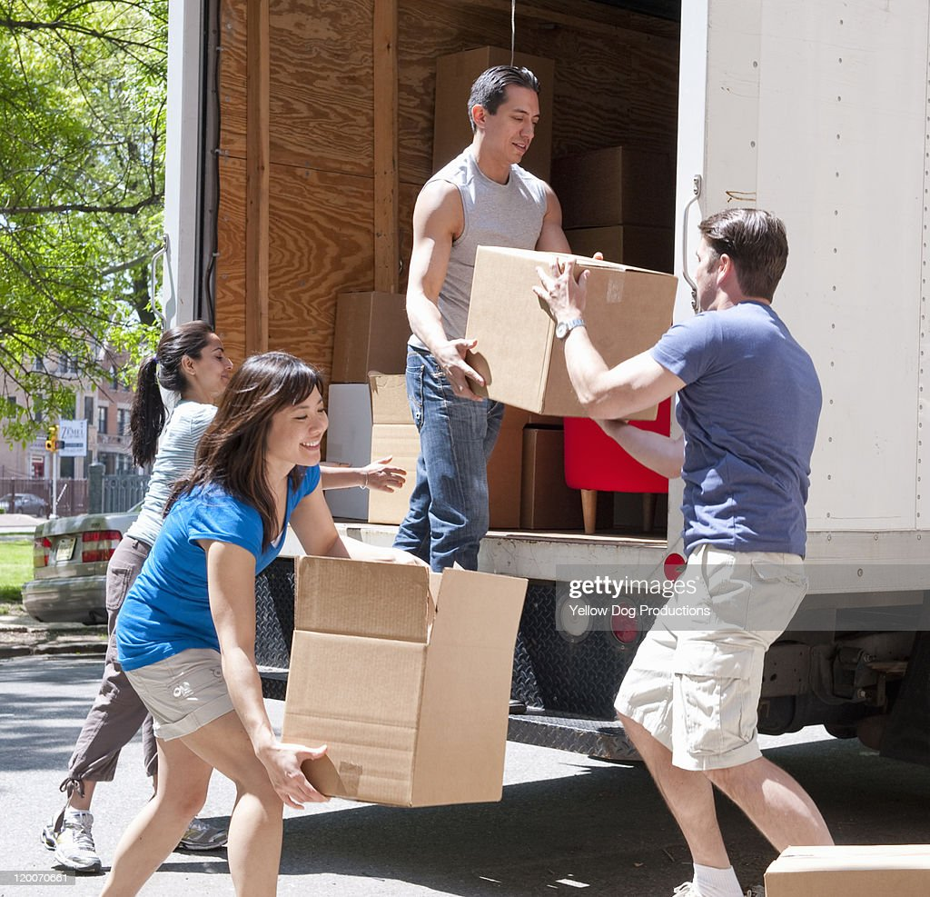Young adults moving boxes from moving truck