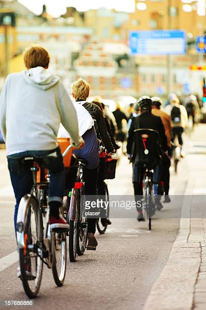 Young adults on bikes in the city, evening traffic