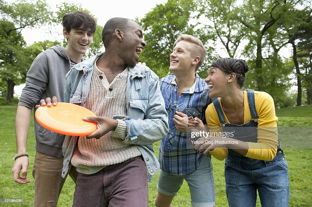 Young adults playing frisbee  in the park