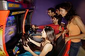 Young adults playing games in amusement arcade