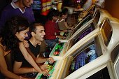 Young adults playing games in video arcade