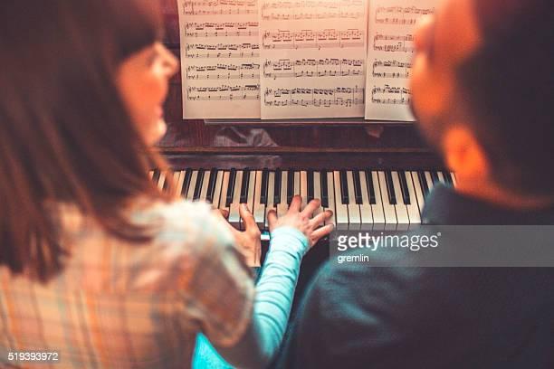 Giovani adulti suona il pianoforte insieme