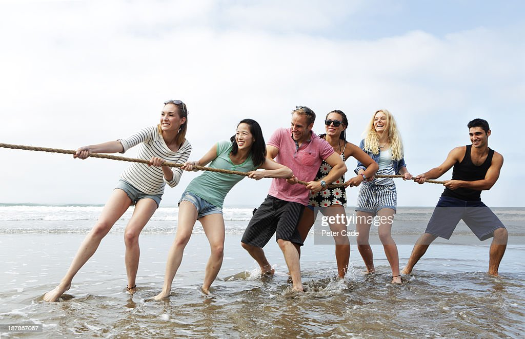 Young adults playing tug 'o' war on beach : Stock Photo