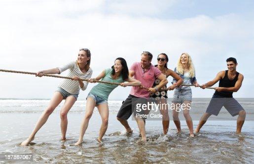 Young adults playing tug 'o' war on beach