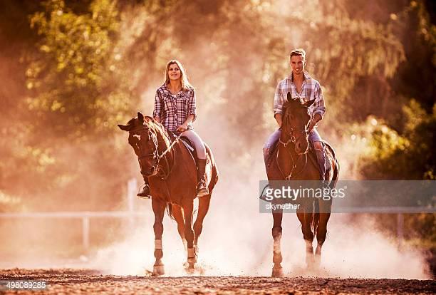 Junge Erwachsene üben mit Pferden.