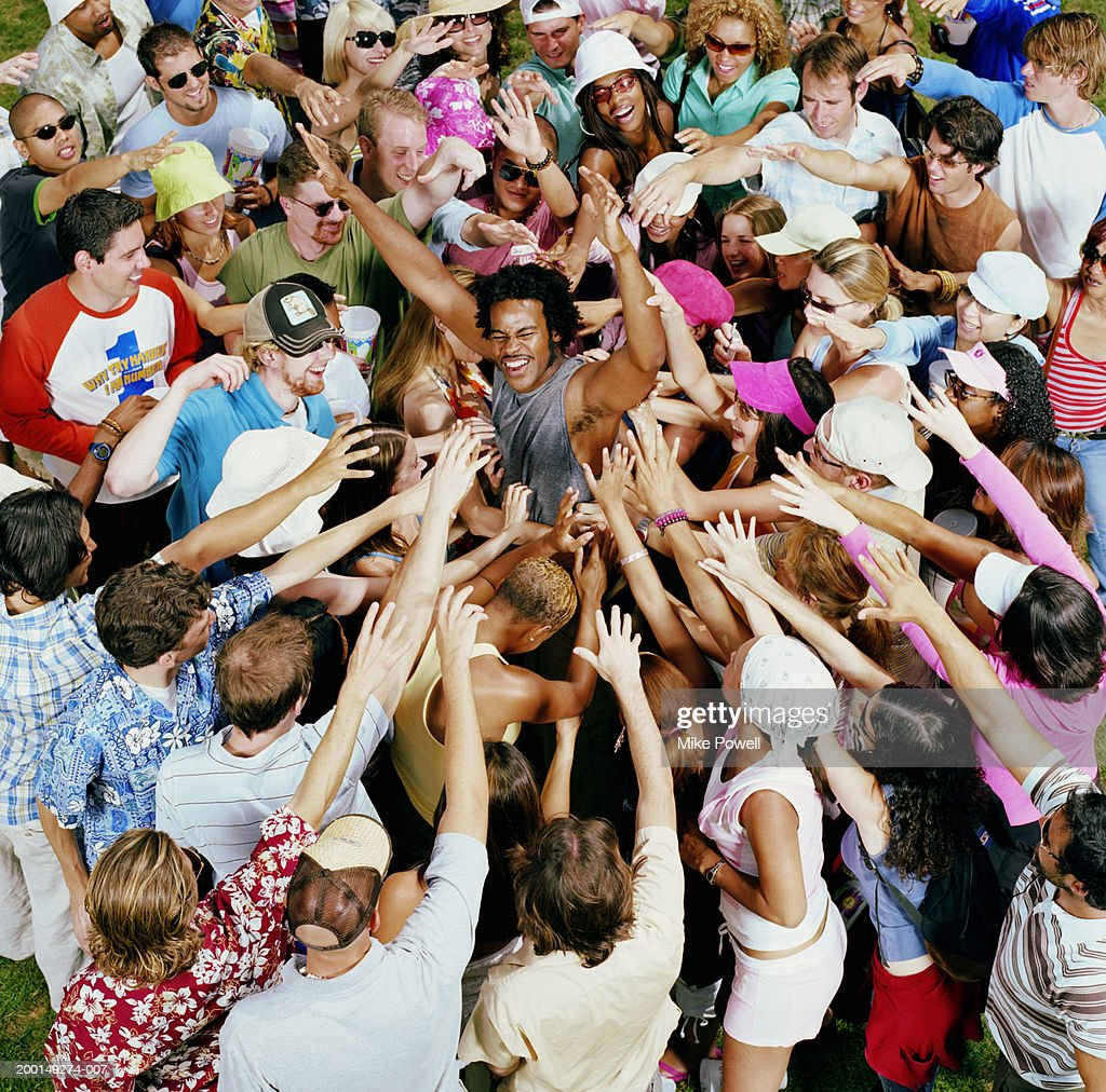 Young adults reaching for male celebrity, elevated view : Stock Photo