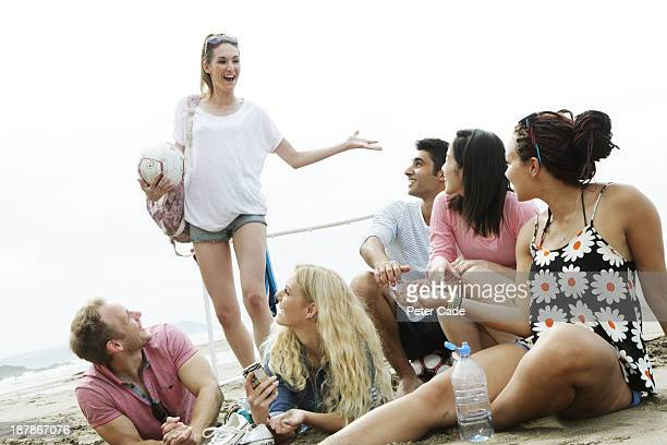 Young adults relaxing on beach, girl arriving