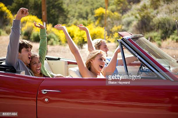 4 young adults riding in car