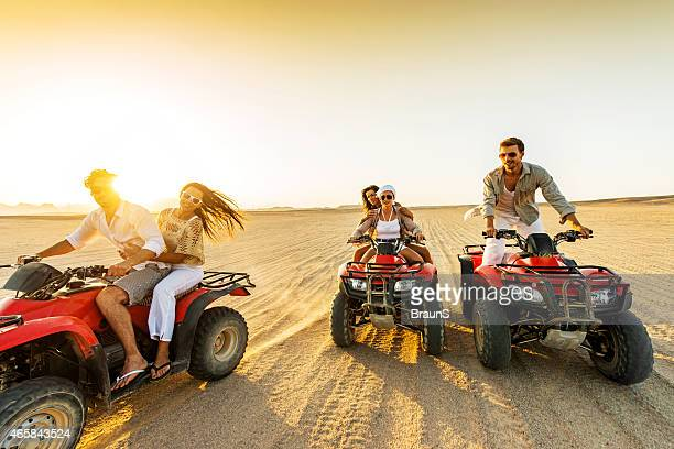 Young adults riding red ATVs in a desert at sunset