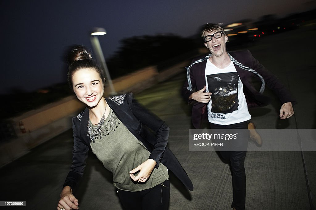 Young adults running at night : Stock Photo