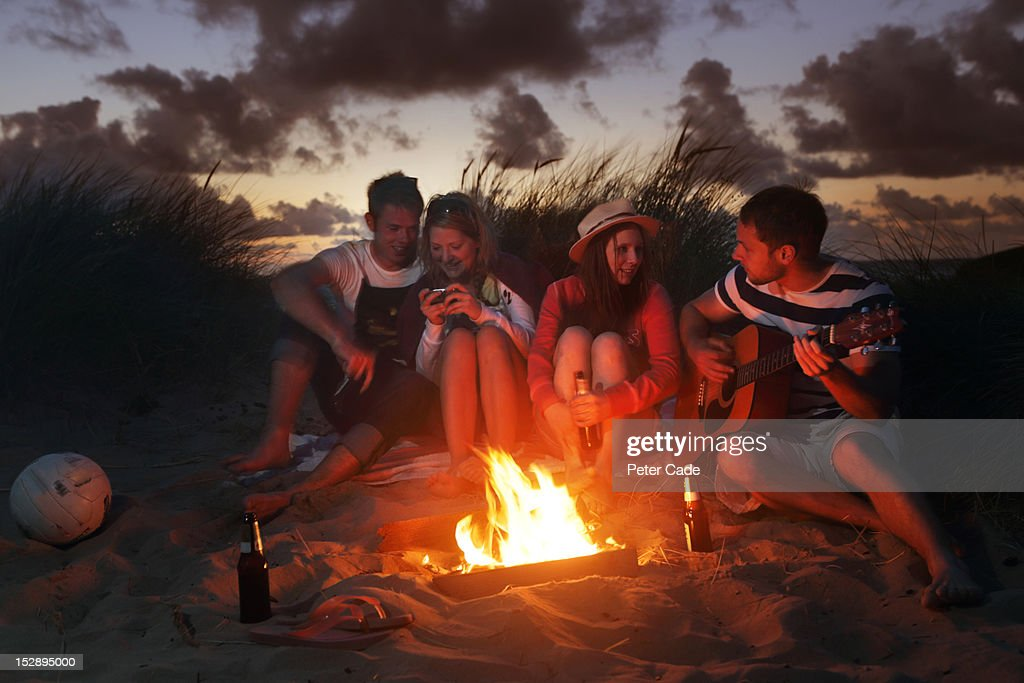 Young adults sat around fire in sand dunes : Stock Photo