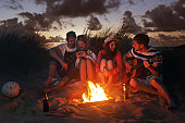 Young adults sat around fire in sand dunes