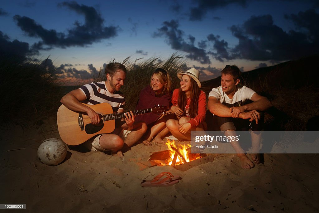 Young adults sat around fire with guitar : Stock Photo