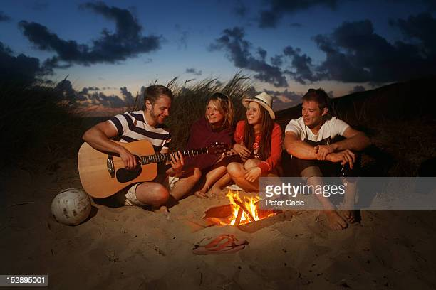 Young adults sat around fire with guitar