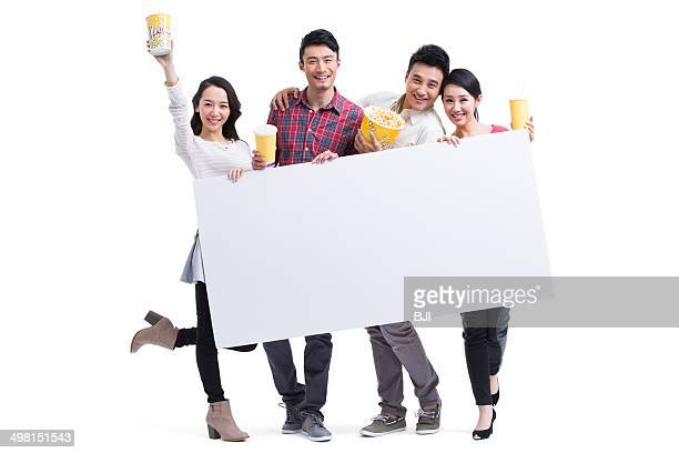Young adults showing white board with popcorn in hands