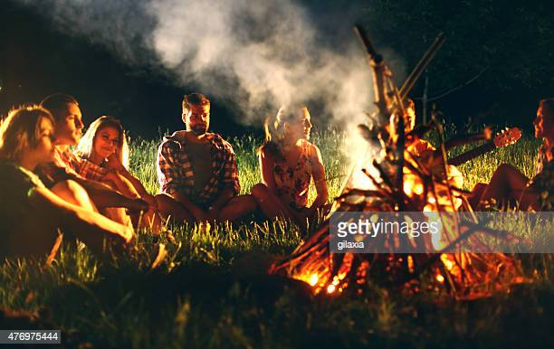 Young adults sitting around campfire.