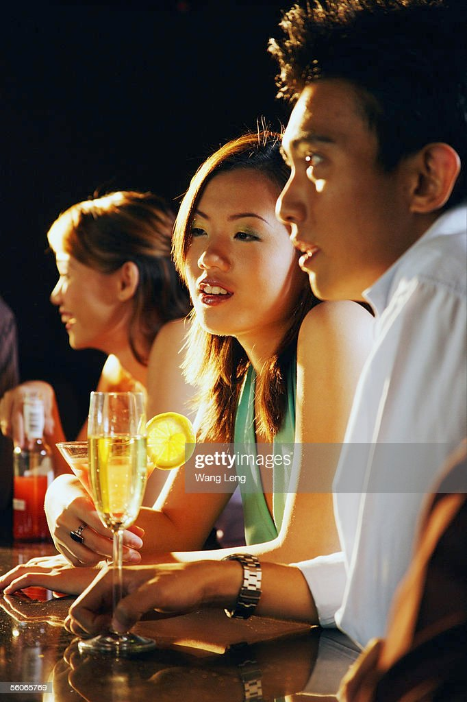 Young adults sitting at bar : Stock Photo