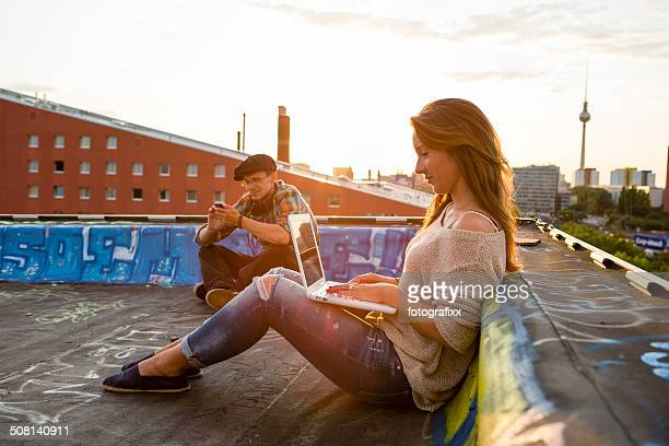young adults sitting on a roof, back lit