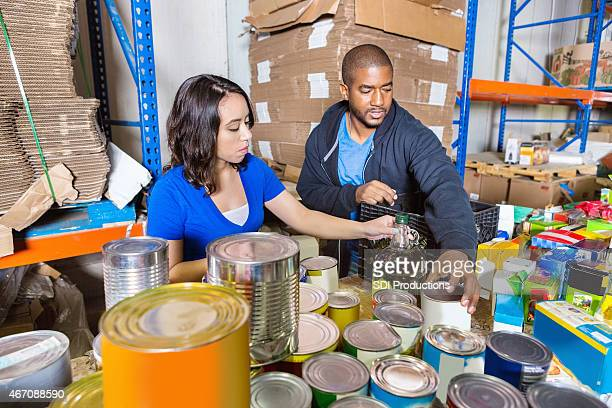 Young adults sorting donated food for charity drive in warehouse