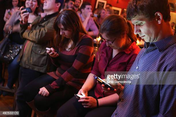 Young adults split their time between the televisied debate and Twitter on their smart phones during a debate watch party at the Local 16 bar and...