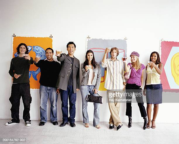 Young adults standing against wall in art gallery, holding up drinks
