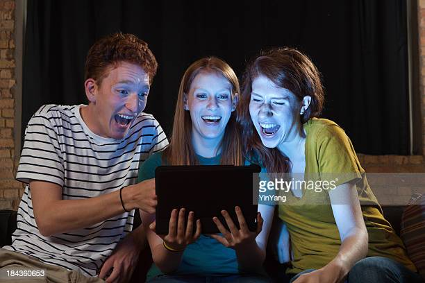 Young Adults Watching Movie on Tablet Computer, Friends Laughing Together