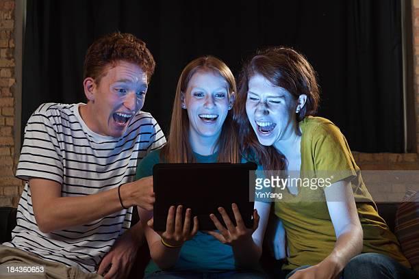 Giovani adulti, guardare film sul Tablet Computer, amici ridere insieme