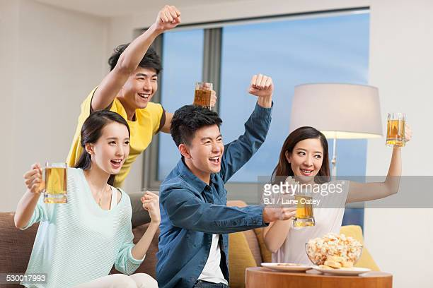 Young adults watching sports games with beer