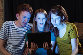 Young Adults Watching Streaming Video Together on Digital Tablet