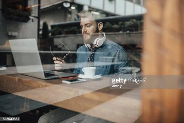 Junge Werbung Artdirector arbeiten am Laptop im Coffee shop