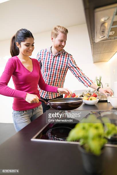 Young affectionate couple cooking healthy meal together and flirting