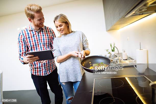 Young affectionate couple preparing healthy food using tablet