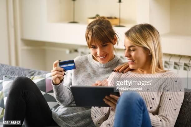 Jeune couple de lesbiennes affectueux shopping en ligne à l'aide de tablette numérique