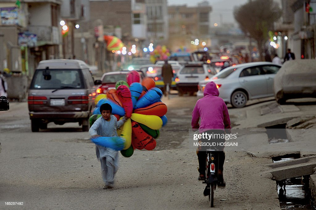 A young Afghan balloon seller runs towards a customer on a street in Kabul on April 2, 2013. Some nine million Afghans or 36 percent of the population are living in 'absolute poverty' while another 37 percent live barely above the poverty line, according to a UN report. AFP PHOTO / Massoud HOSSAINI