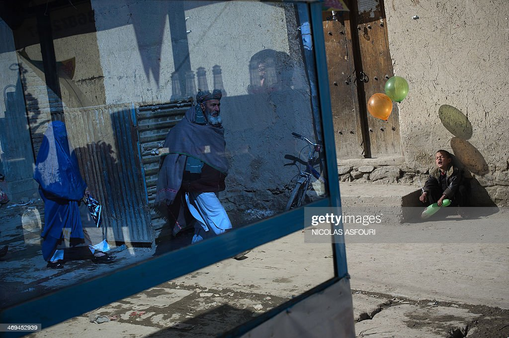 A young Afghan balloon vendor (R) grimaces as he waits for costumers on a street as pedestrians are reflected in the window of a chicken soup mobile canteen in Kabul on February 15, 2014. Some nine million Afghans or 36 percent of the population are living in 'absolute poverty' while another 37 percent live barely above the poverty line, according to a UN report. AFP PHOTO/ Nicolas ASFOURI