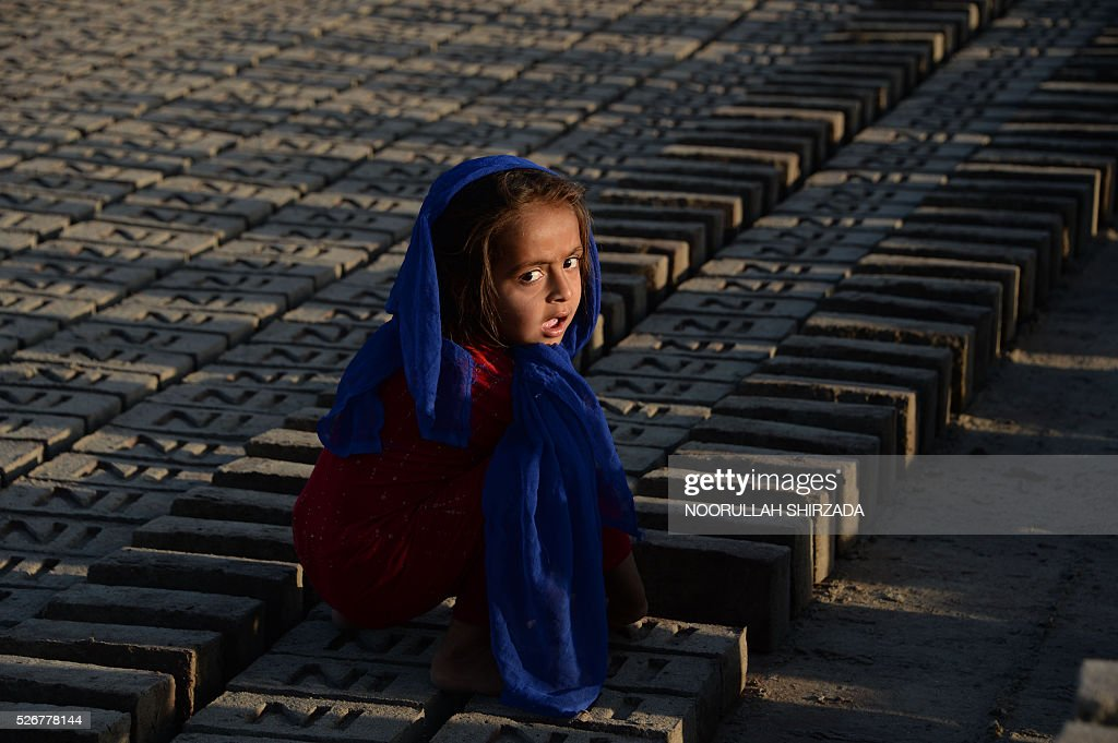 A young Afghan child sorts bricks at a traditional brick factory during International Labour Day on the outskirts of Jalalabad on May 1, 2016. International Labour Day is marked annually on May 1. / AFP / NOORULLAH