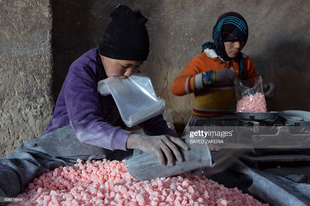 Young Afghan employees work at a traditional sweet factory in Ghazni on February 6, 2016. AFP PHOTO / Sayed Zakeria / AFP / SAYED ZAKERIA