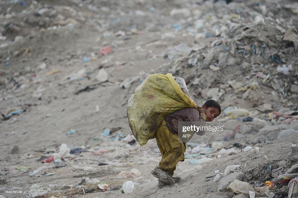 A young Afghan garbage collector carries recyclable material from a landfill in the outskirts of Kabul on October 17, 2012. Over a third of Afghans are living in abject poverty, as those in power are more concerned about addressing their vested interests rather than the basic needs of the population, a UN report said.