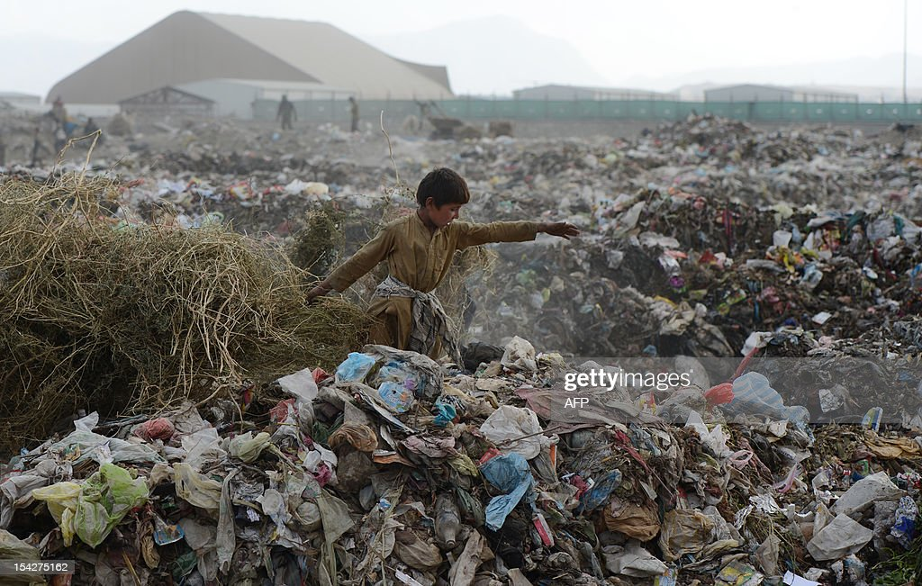 A young Afghan garbage collector looks for recyclable material from a landfill in the outskirts of Kabul on October 17, 2012. Over a third of Afghans are living in abject poverty, as those in power are more concerned about addressing their vested interests rather than the basic needs of the population, a UN report said. AFP PHOTO / JAWAD JALALI