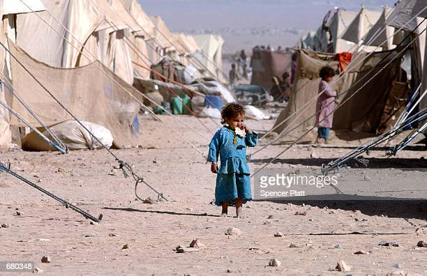 A young Afghan girl eats a piece of bread at the Chaman refugee camp November 8 2001 on the Pakistan border with Afghanistan The UNHCR has estimated...