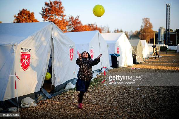 A young Afghan girl plays outside tents prior moving into a weatherresistant accommodation facility at a shelter for asylumseekers on October 27 2015...