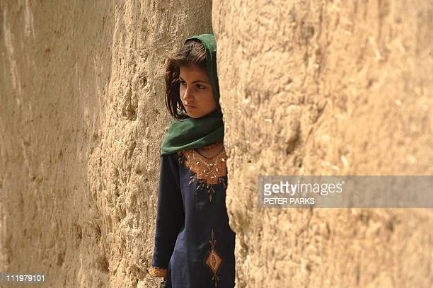 A young Afghan girl stands outside her house on a street in the town of Musa Qala in Helmand province on April 9 2011 Afghanistan said recently its...