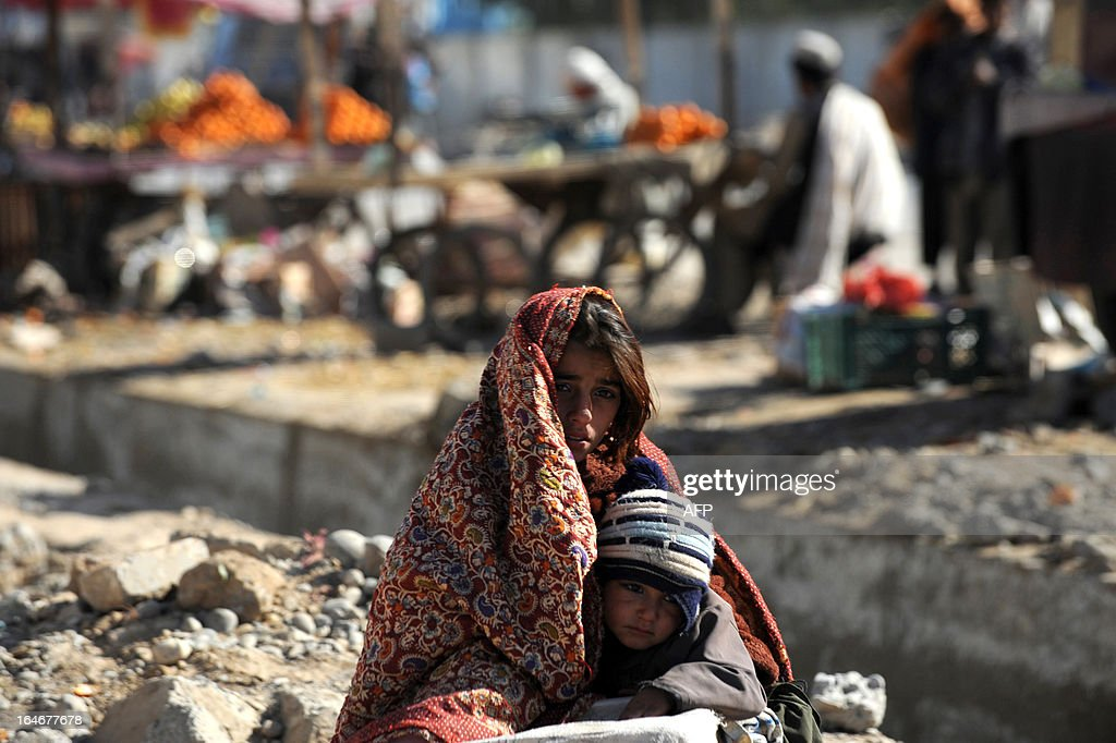 A young Afghan woman holds a child as they wait for a taxi on a street in Kandahar on March 25, 2012. Afghanistan is having trouble keeping hard-earned development gains due to looming security challenges when NATO military forces withdraw in 2014, an internal World Bank audit said.
