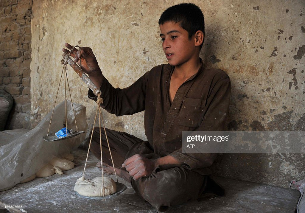 A young Afghan worker uses a set of scales to weigh dough at a traditional bread factory in Jalalabad on November 13, 2012. The bread of Afghanistan is usually oval or rectangular and baked in a tandoor, a cylindrical oven and served with most meals in the Central Asian nation. AFP PHOTO/Noorullah Shirzada
