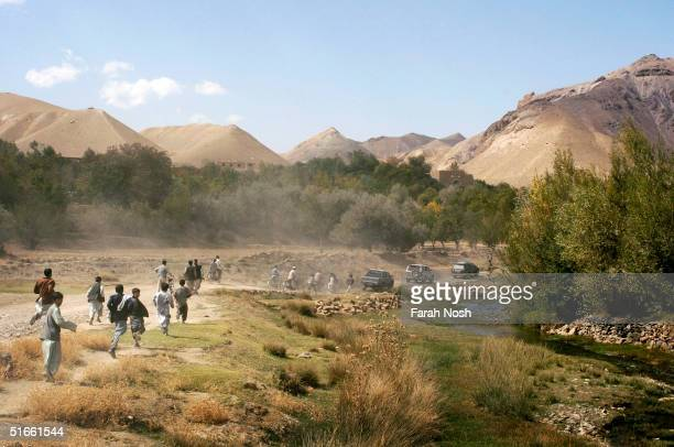 Young Afghans from the village of Surkhah Parsa run after the campaign convoy of Afghanistan's only female presidential candidate Dr Massouda Jalal...
