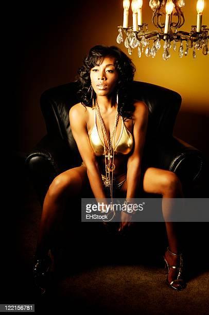 Giovane afro-americano modello di Bikini oro con Bling lampadario sedia in pelle